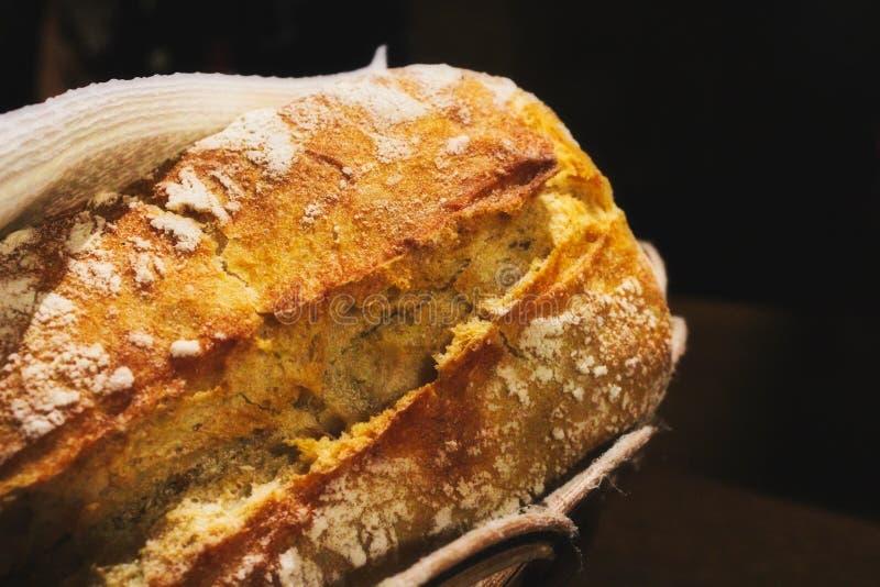 Vers gebakken rustiek wit het broodbroodje van het tarwemeelbrood in een mand tegen een zwarte achtergrond stock afbeeldingen