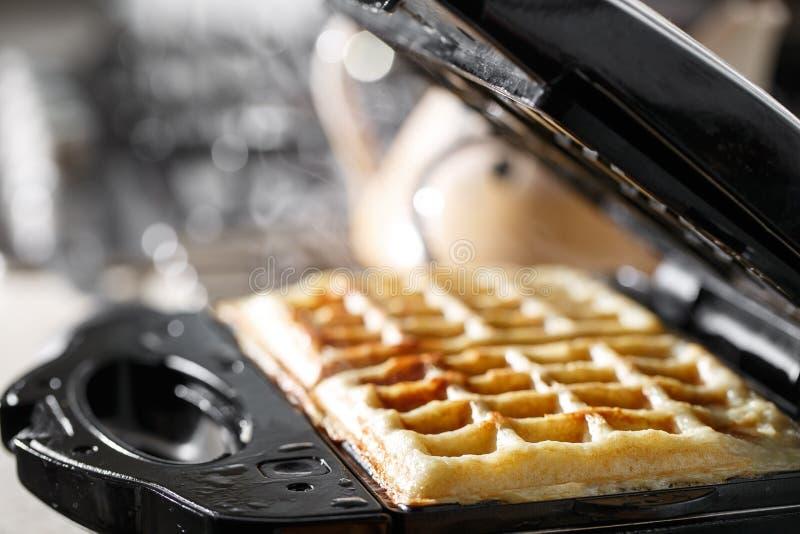 Vers gebakken traditionele Belgische wafels in de maker van de ijzerwafel stock afbeelding
