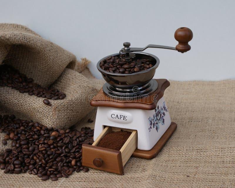 Vers gemalen bonenkoffie op de traditionele manier in een oude koffiemolen stock afbeelding