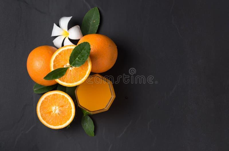 Vers gesneden sinaasappel en jus d'orange op zwarte royalty-vrije stock afbeelding