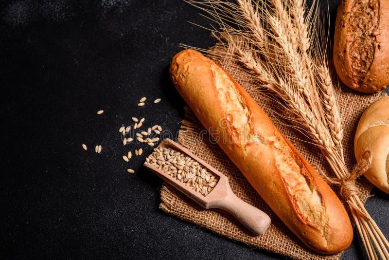 Vers geurig brood met korrels en kegels van tarwe tegen een donkere achtergrond stock fotografie