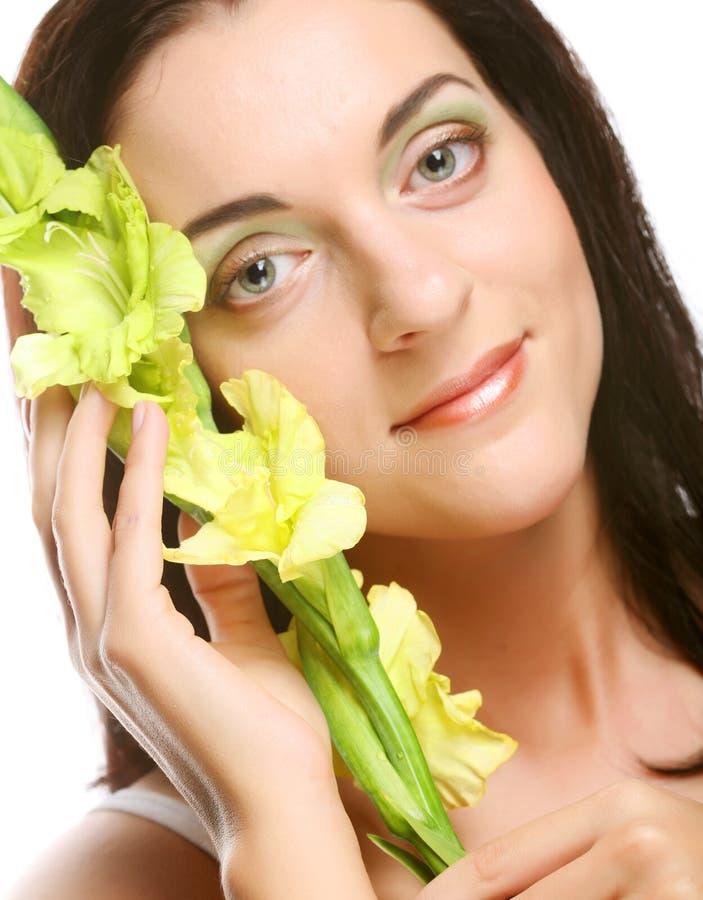 Vers gezicht met gladiolenbloemen in haar handen stock foto