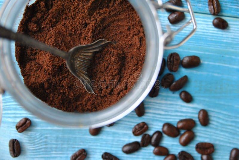 Vers grondkoffie in een glaskruik, oude metaallepel en verspreid rond koffiebonen stock foto's