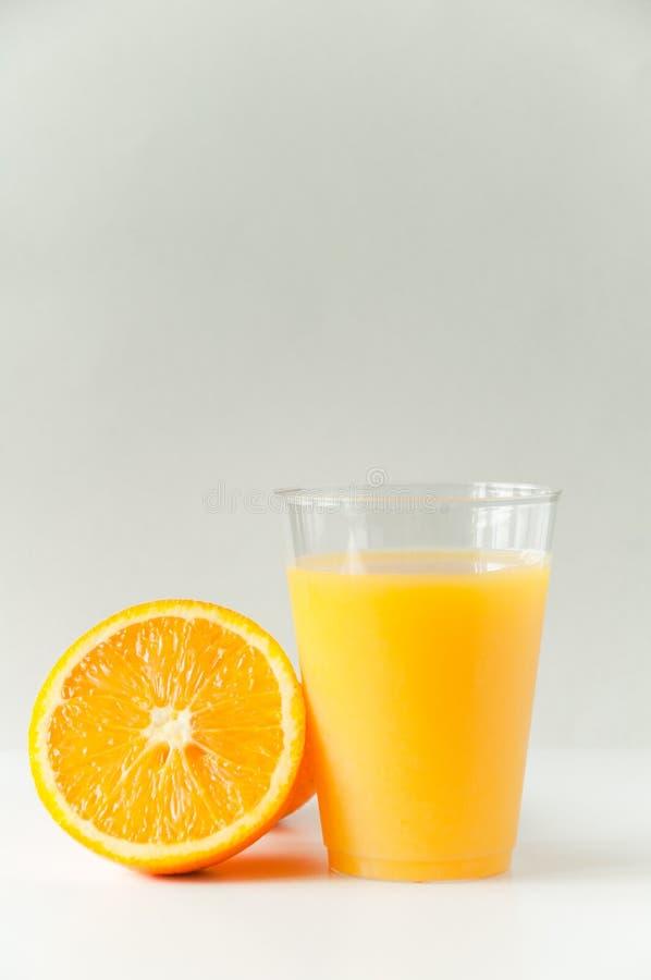 Vers jus d'orange in een glas Ronde oranje plakken op een witte achtergrond Achtergrond van het citrusvruchten de tropische fruit royalty-vrije stock afbeelding