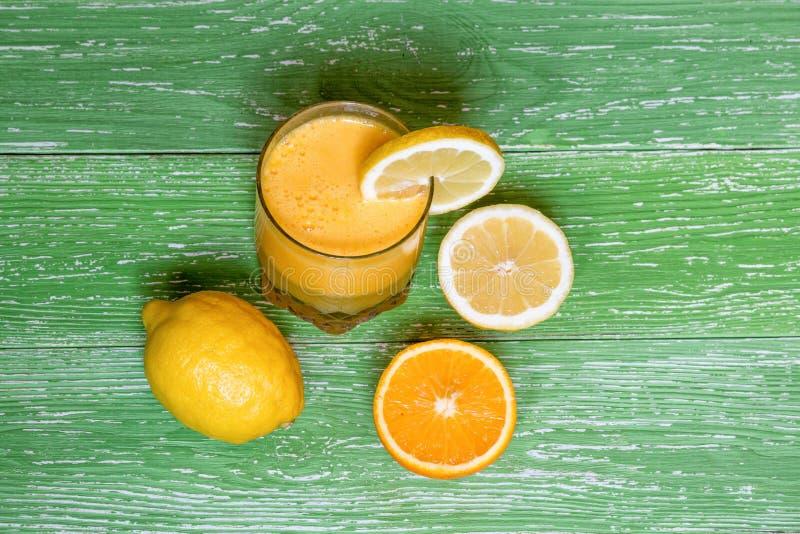 Vers jus d'orange in glas, citroen, sinaasappel op groene houten backg royalty-vrije stock foto