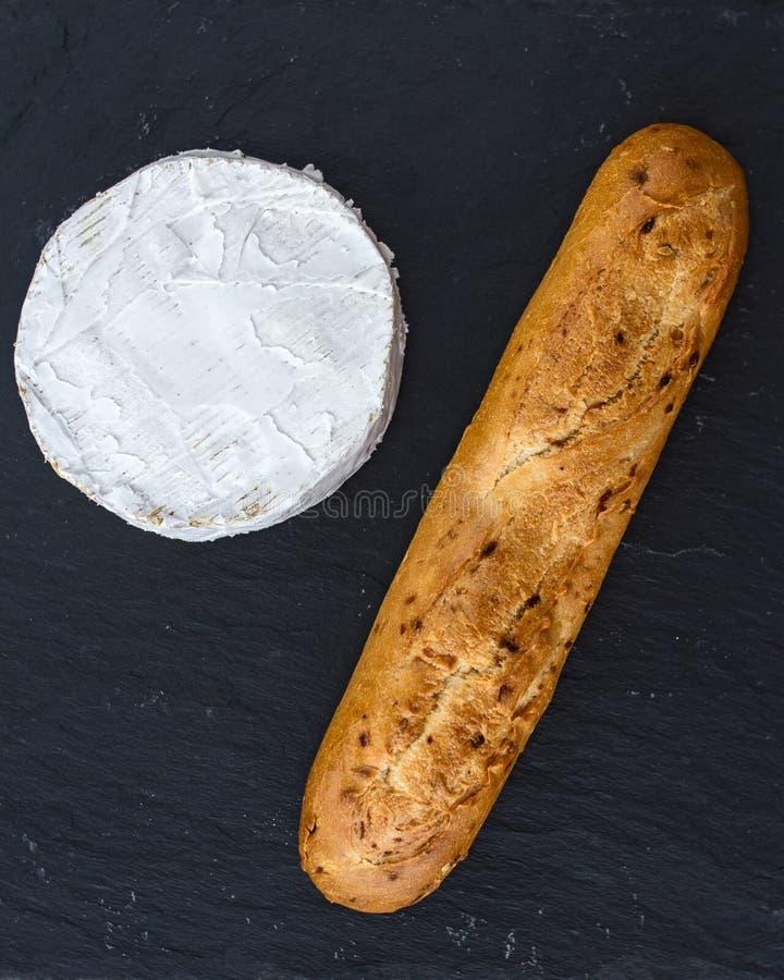 Vers knapperig baguette en hoofd van Zwitserse Camembert op een zwarte geweven achtergrond royalty-vrije stock fotografie