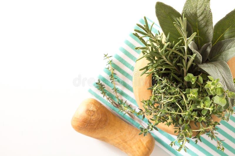 Vers kruidenboeket in houten mortier op gevouwen keukenhanddoek, op witte achtergrond stock afbeelding