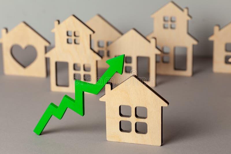 Vers le haut de la flèche et de beaucoup de maisons Croissance sur le marché des prix d'immobiliers Achetant et vendant la maison photographie stock
