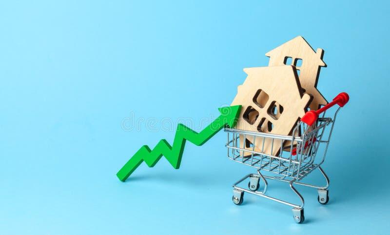 Vers le haut de la flèche et des maisons dans le caddie sur le fond bleu Croissance du marché des prix d'immobiliers photos libres de droits