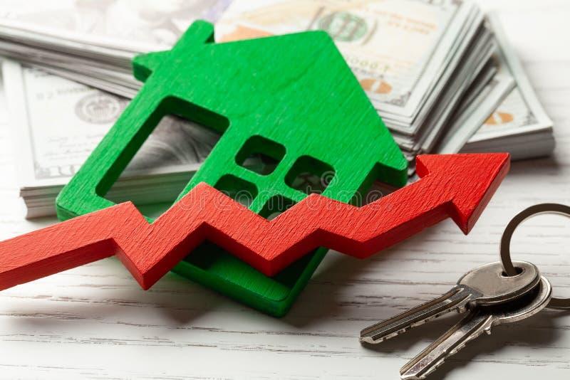 Vers le haut de la flèche et de la maison avec l'argent sur le fond en bois blanc Croissance du march? des prix d'immobiliers photo libre de droits