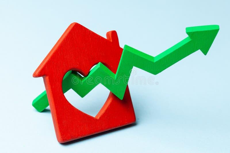 Vers le haut de la flèche et de la maison sur le fond bleu Croissance du march? des prix d'immobiliers photo stock