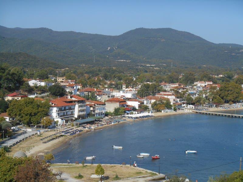 Vers le haut de la vue vers la plage de ville du ` s d'Olympiada, peu de bateaux de pêche, de montagne et la mer bleue lumineuse photographie stock libre de droits