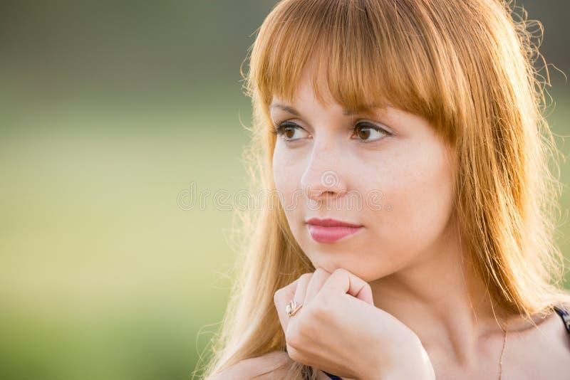 Vers le haut du portrait d'une fille regardant fixement vers la gauche, créant un fond vert mou photo stock