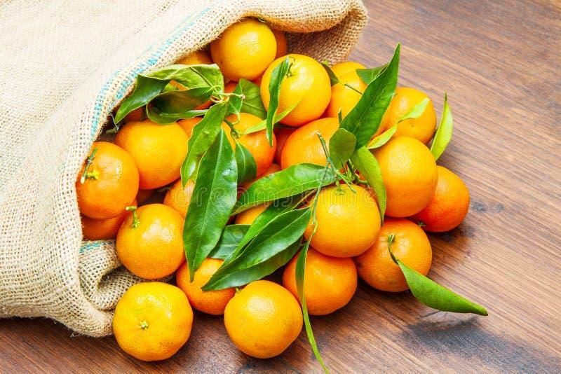 Vers mandarijntjesfruit met bladeren op houten lijst stock afbeeldingen