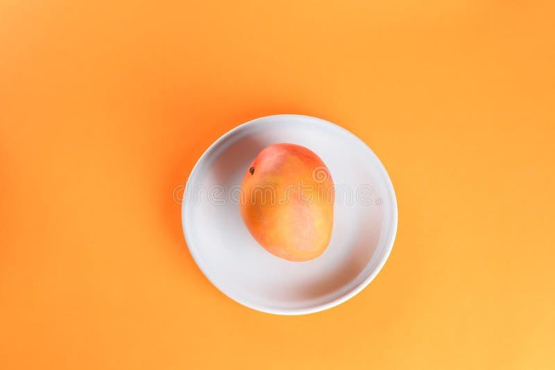 Vers mango tropisch fruit op plaat op oranje achtergrond royalty-vrije stock afbeeldingen