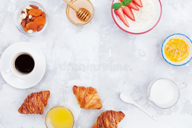 Vers ochtendontbijt met koffie, croissant, havermeel, jam, honing en sap op de bovenkantmening van de steenlijst Vlak leg royalty-vrije stock foto's
