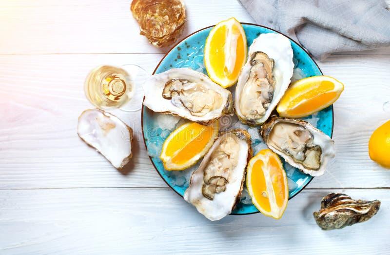 Vers oestersclose-up op blauwe plaat, gediende lijst met oesters, citroen en champagne in restaurant Gastronomisch voedsel stock foto