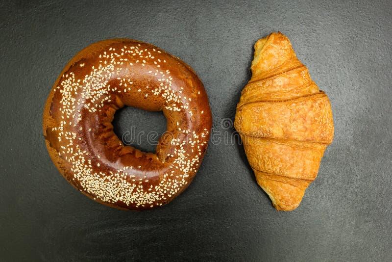 Vers ongezuurd broodje en croissant op een zwarte achtergrond stock foto