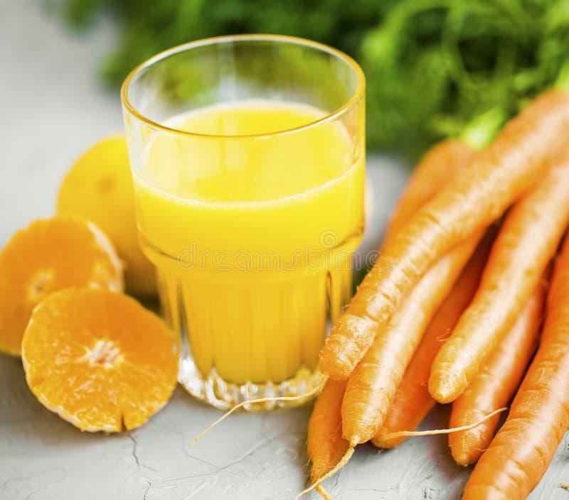 Vers organisch wortel en jus d'orangeglas, gezond levensstijlconcept en detox sappen stock afbeeldingen