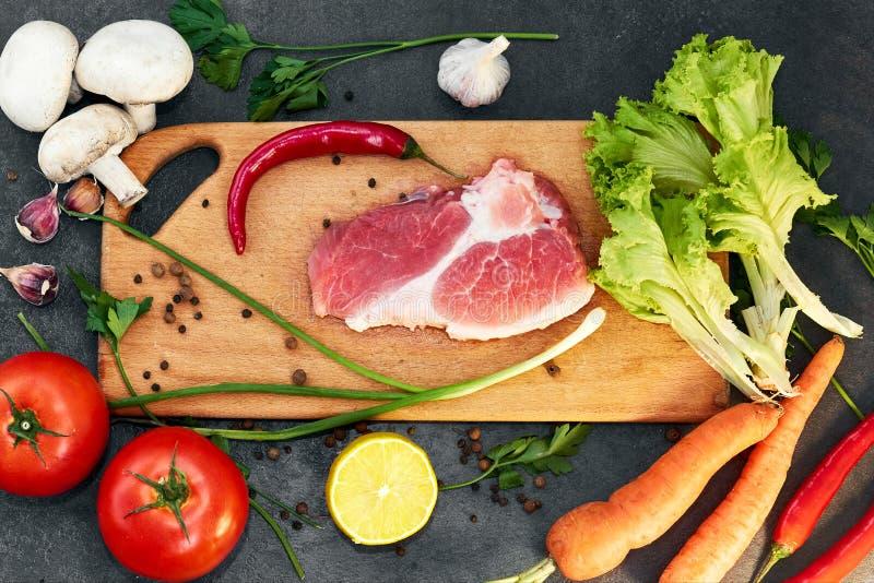 Vers rundvleeslapje vlees, houten lepel, Assortiment van Verse Groenten, aromatische kruiden, kruiden en groenten voor het koken, royalty-vrije stock foto