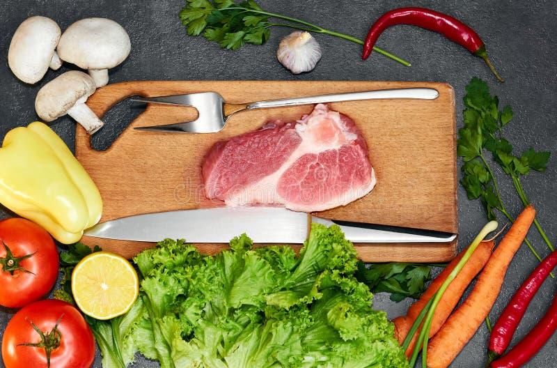 Vers rundvleeslapje vlees, houten lepel, Assortiment van Verse Groenten, aromatische kruiden, kruiden en groenten voor het koken, stock foto