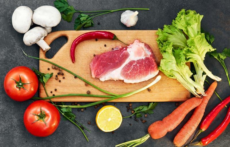 Vers rundvleeslapje vlees, houten lepel, Assortiment van Verse Groenten, aromatische kruiden, kruiden en groenten voor het koken, royalty-vrije stock foto's