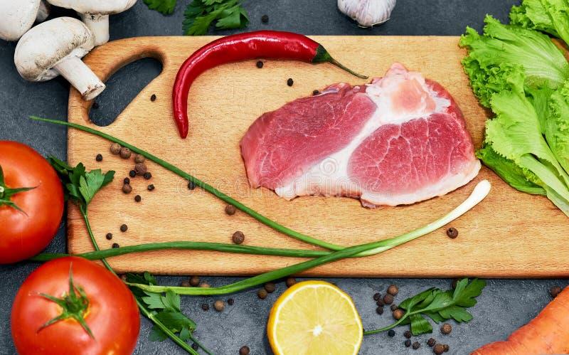 Vers rundvleeslapje vlees, houten lepel, Assortiment van Verse Groenten, aromatische kruiden, kruiden en groenten voor het koken, stock fotografie