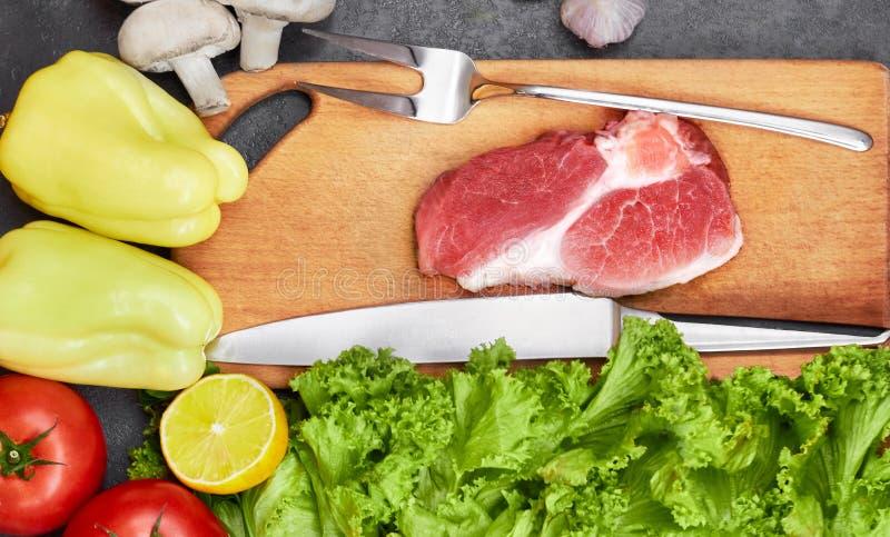 Vers rundvleeslapje vlees, houten lepel, mes en Assortiment van Verse Groenten, aromatische kruiden, kruiden en groenten voor het royalty-vrije stock foto's