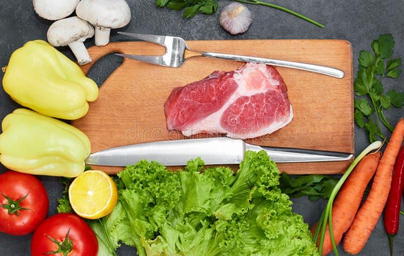 Vers rundvleeslapje vlees, houten lepel, mes en Assortiment van Verse Groenten, aromatische kruiden, kruiden en groenten voor het royalty-vrije stock fotografie