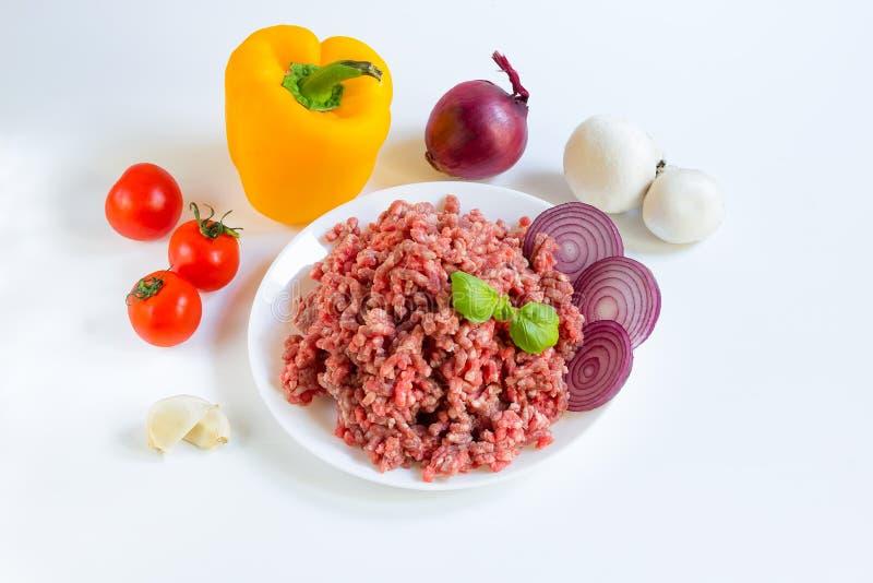Vers ruw fijngehakt rundvlees in een witte plaat dicht omhoog met peper, ui en tomaten, ruwe ingrediënten voor gevulde peper royalty-vrije stock fotografie