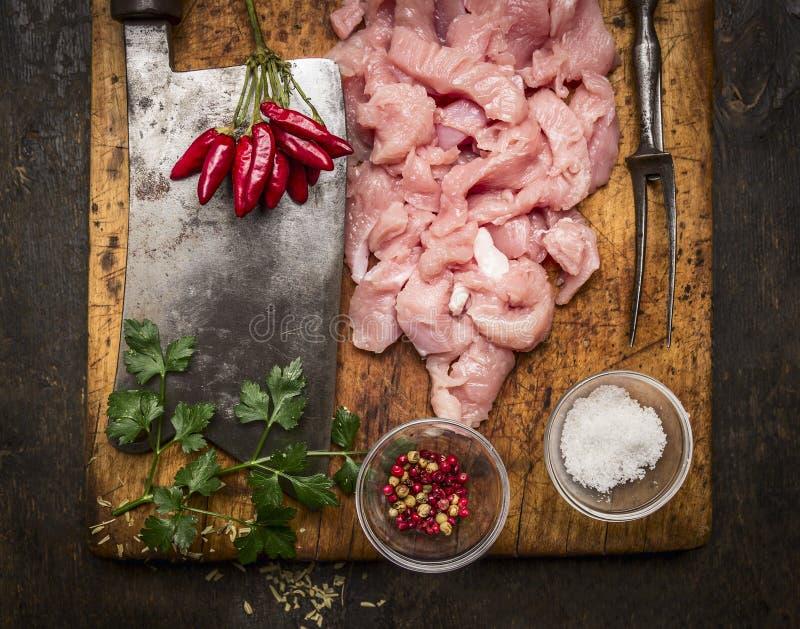 Vers ruw gehakt Turkije, vleesmes, vleesvork, zout, peper, hete peper en verse kruiden op een houten scherpe raad op rustiek w royalty-vrije stock fotografie