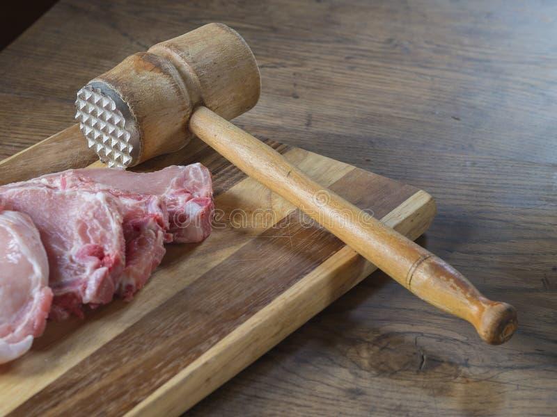 Vers ruw varkenskotelettenvlees met oude vleeshouten hamer op het hakken beer royalty-vrije stock fotografie