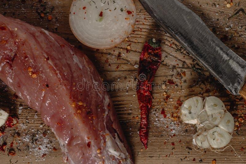 Vers ruw varkensvleeshaasbiefstuk op houten scherpe raad met ui, knoflook en mes stock fotografie
