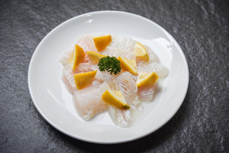 Vers ruw visfiletstuk met citroen op witte plaat - sluit pangasius dolly omhoog visvlees royalty-vrije stock fotografie