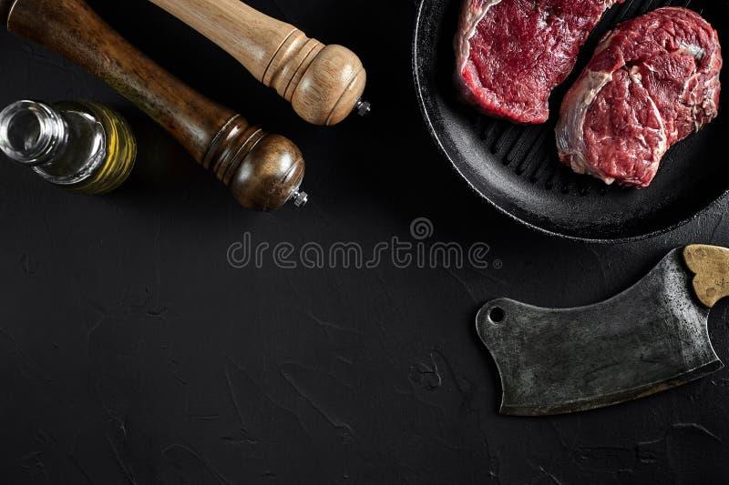 Vers ruw vlees Een stuk van rundvleeshaasbiefstuk op grillpan, met een scherpe bijl, met kruiden voor het koken op zwarte steenli royalty-vrije stock afbeeldingen