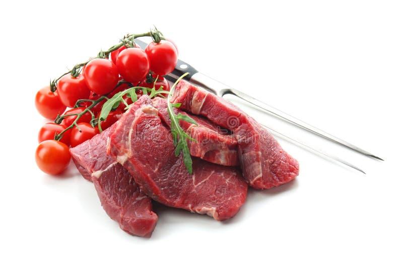 Vers ruw vlees met vork, arugula en tomaten op witte achtergrond royalty-vrije stock afbeeldingen