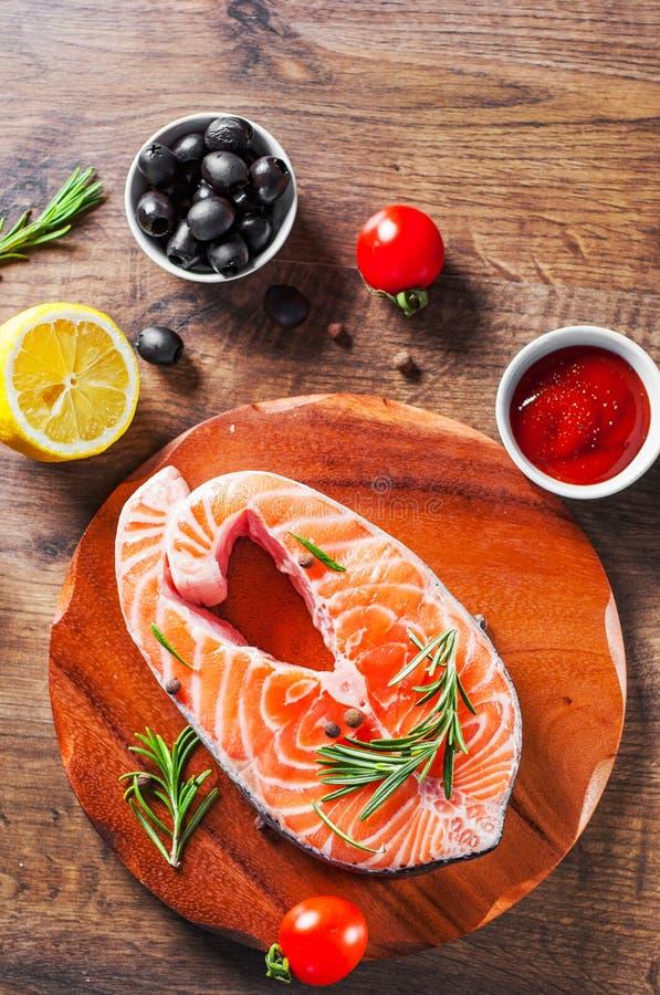 Vers ruw zalmlapje vlees met tomaat, citroen, olijf, peper, saus en aromatische kruiden op de houten lijst stock fotografie