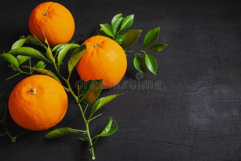 Vers sinaasappel en blad op zwarte achtergrond stock fotografie