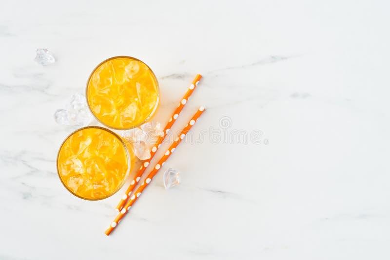 Vers sinaasappel, mango of citroensap in lang glas op witte marmeren achtergrond stock foto's