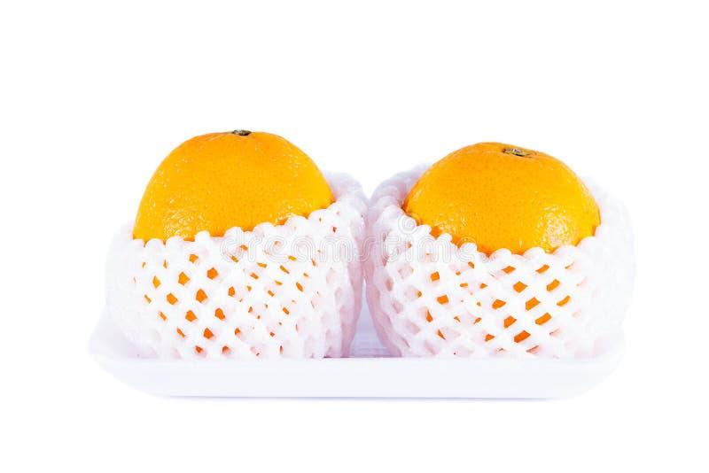 Vers sinaasappelenfruit in schuimbescherming netto op een schuimdienblad isolat stock foto