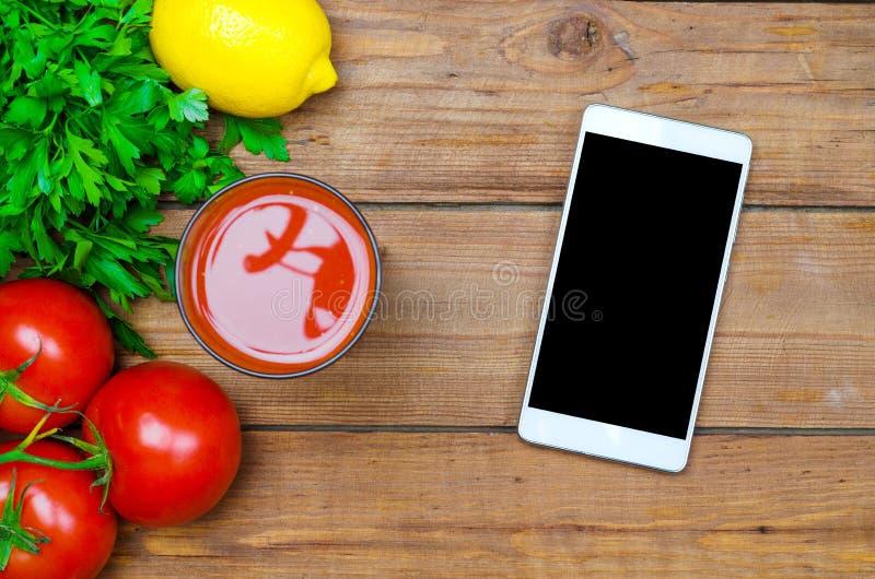 Vers tomatesap, tomaten en mobiel op een houten lijstbovenkant vi stock afbeeldingen