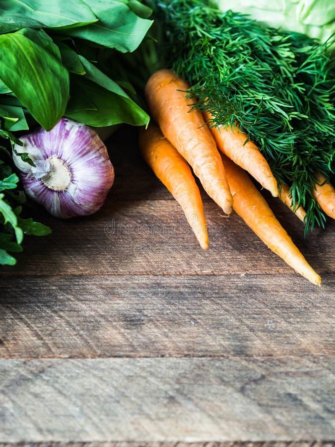 Vers van de Lentegroenten en kruiden kader op houten rustieke achtergrond De lenteoogst van verse groenten De ruimte van het exem stock foto's