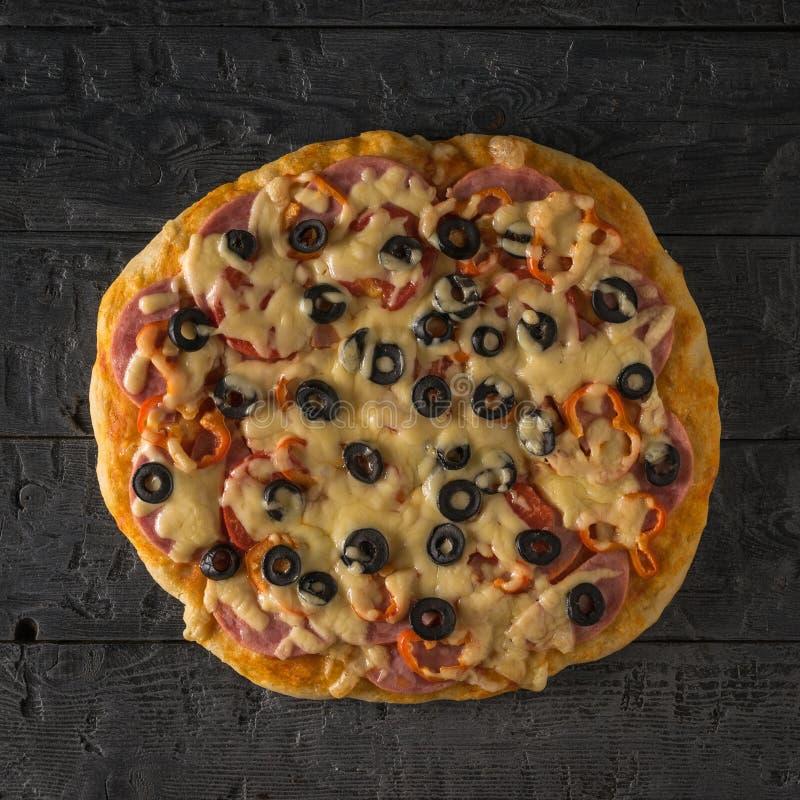 Vers voorbereide eigengemaakte pizza met olijven, worst en paddestoelen op een houten lijst De mening vanaf de bovenkant royalty-vrije stock fotografie