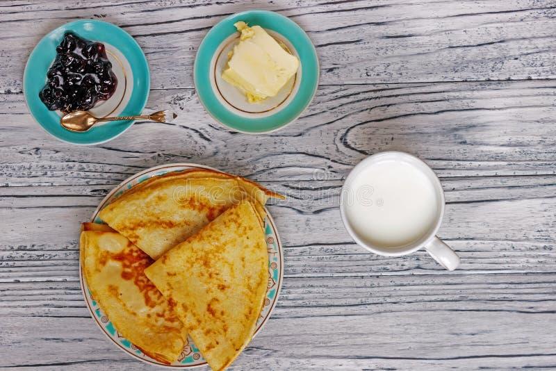 Vers voorbereide pannekoeken voor ontbijt dichtbij jam, een glas melk en boter, hoogste horizontale mening, royalty-vrije stock afbeeldingen