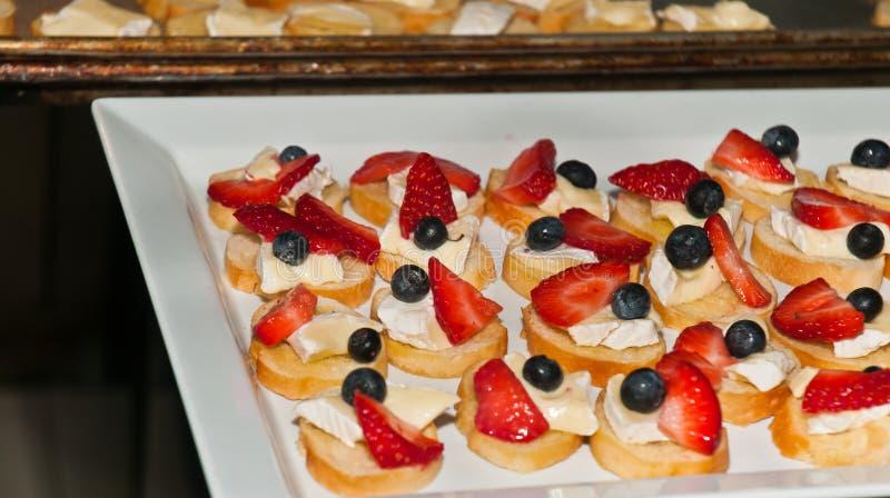 Vers voorbereidingen getroffen appitizer van gesneden baguette met kaas, bosbes, en gehalveerde aardbei stock afbeeldingen