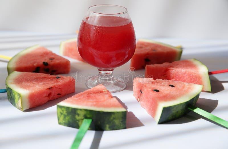 Vers watermeloensap in een glas met een stro en gesneden watermeloen †‹â€ ‹met gekleurde stokken stock fotografie