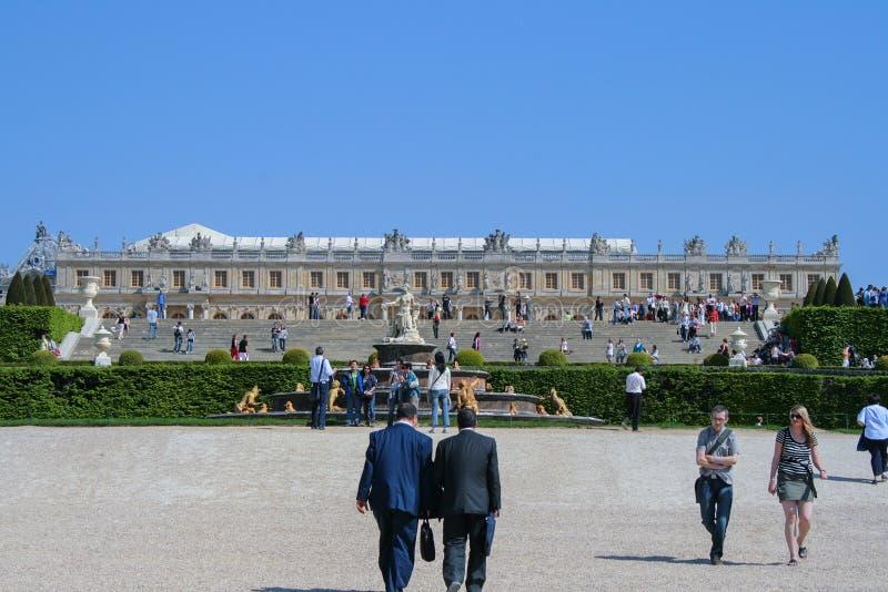 05 05 2008 Versailles, Frankrike Turister som omkring går, parkerar på bakgrund av slotten arkivbild