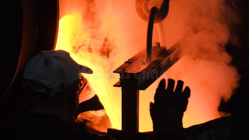 Versamento d'acciaio caldo nell'acciaieria Metraggio di riserva Metallo scorrente alla fonderia Versamento del metallo liquido in fotografia stock