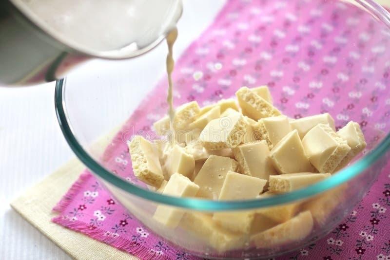 Versamento della crema calda ai pezzi di cioccolata bianca fotografia stock libera da diritti