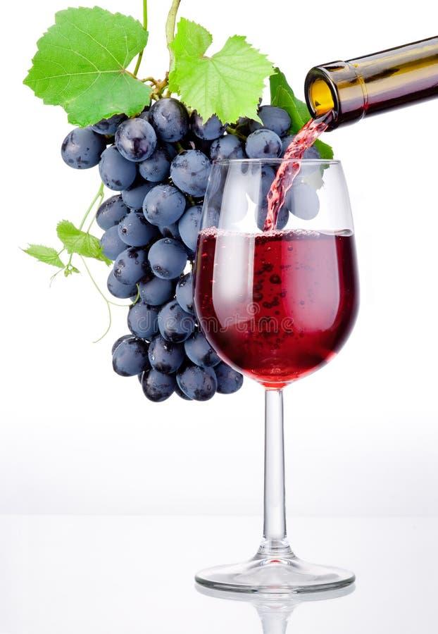 Versamento un vetro di vino rosso e del mazzo di uva con le foglie fotografie stock libere da diritti